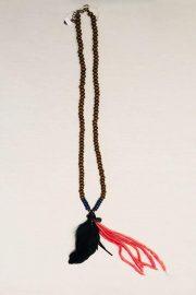 Collar de cuentas en madera largo, detalle de pluma y algodón.