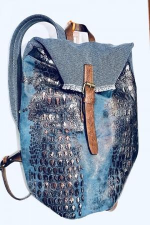 Mochila en azul y cuero, con asa para llevarla también de mano.
